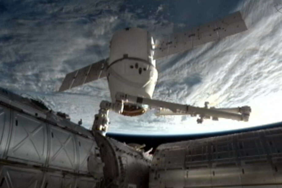 This NASA-TV image shows the SpaceX Dragon cargo ship being moved away from the International Space Station with its robotic arm near the end of Dragon's resupply mission. Photo: NASA / Associated Press