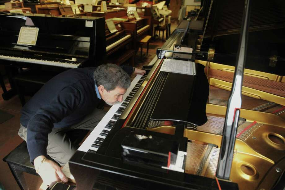 Evan Tublitz, owner of Used Piano Center, pulls out the keys on a 1983 Young Chang piano at his shop on Park Ave. on Tuesday, March 26, 2013 in Mechanicville, NY.  (Paul Buckowski / Times Union) Photo: Paul Buckowski