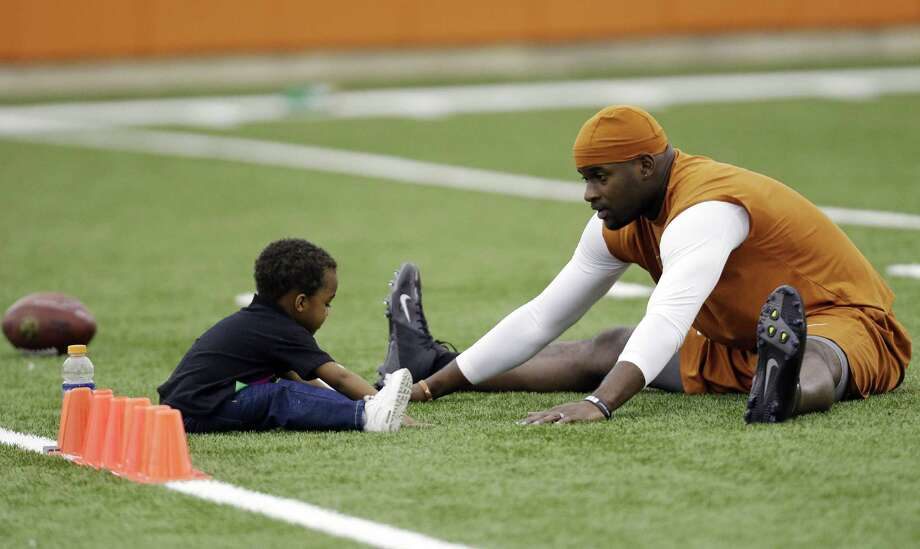 Vince Young stretches with son Jordan, 2, prior to working out at Texas' pro day in an effort to land a spot on an NFL team. Representatives from 30 squads were in attendance Tuesday. Photo: Eric Gay / Associated Press