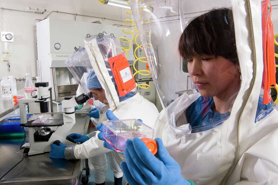 """Researcher Nadya Yun works with an infectious agent while wearing a white plastic """"space suit"""" topped with a transparent, flexible helmet. All air travels through special filters as it enters and leaves the building. / Handout"""
