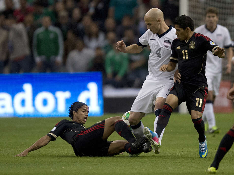 Mexican forwards Giovani Dos Santos (L) and Javier Aquino (R) vie for the ball US defender Michael Bradley. Photo: YURI CORTEZ, AFP/Getty Images / YURI CORTEZ