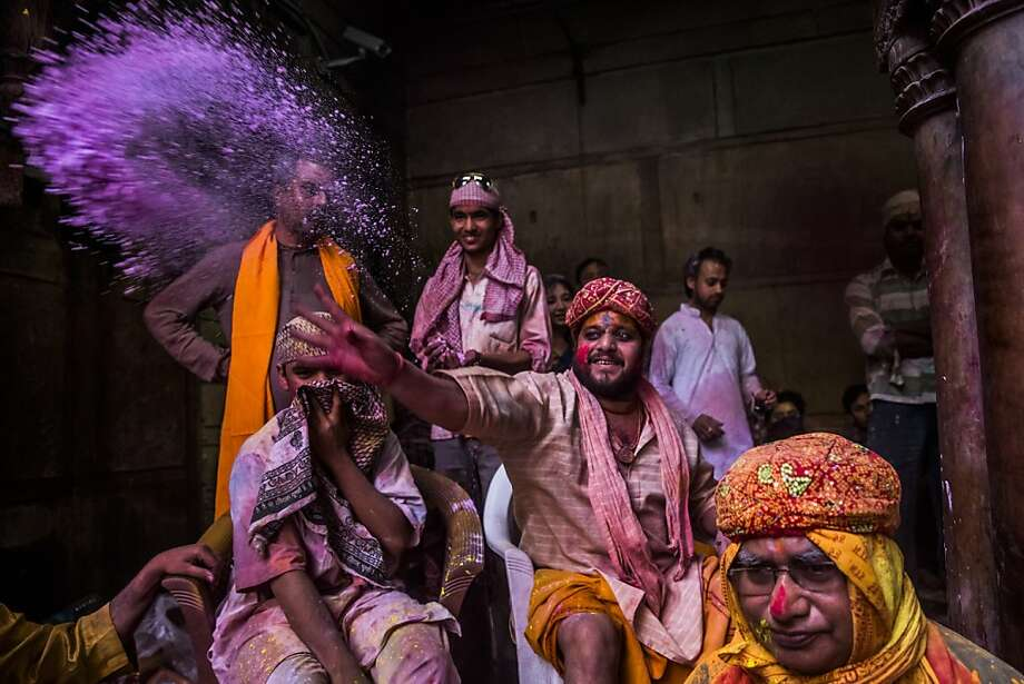 VRINDAVAN, INDIA - MARCH 26: A Hindu priest throws coloured powder at devotees during Holi celebrations, at the Banke Bihari temple on March 26, 2013 in Vrindavan, India. The tradition of playing with colours on Holi draws its roots from a legend of Radha and the Hindu God Krishna. It is believed that young Krishna was jealous of Radha's fair complexion since he himself was very dark. After questioning his mother Yashoda on the darkness of his complexion, Yashoda, teasingly asked him to colour Radha's face in which ever colour he wanted. In a mischievous mood, Krishna applied colour on Radha's face. The tradition of applying color on one's beloved is being religiously followed till date. (Photo by Daniel Berehulak/Getty Images) Photo: Daniel Berehulak, Getty Images