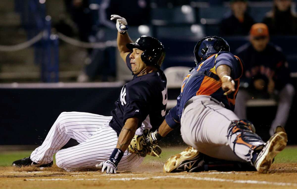 The Astros' Carlos Corporan tags out the Yankees' Juan Rivera, who was trying to score in the sixth.