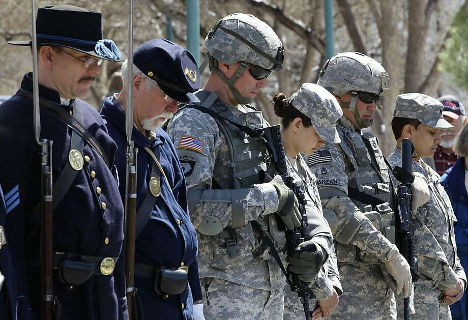 Members of a ceremonial unit portraying Colorado volunteers who fought for the Union in the Civil War, left, stand with Colorado National Guard soldiers of the 169th Fires Brigade, during a prayer at a ceremony marking 150 years since the Battle of Glorieta Pass, a U.S. Civil War battle between the 1st Colorado Regiment Volunteers and Texas Confederate forces, at the Civil War Memorial on the steps of the state Capitol, in Denver, Tuesday, March 26, 2013. The battle would become the site of the westernmost battleground of the Civil War. (AP Photo/Brennan Linsley) Photo: Brennan Linsley, Associated Press