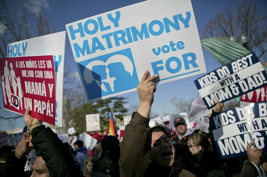Opponents of same-sex marriage hold signs while demonstrating outside the U.S. Supreme Court in Washington. Photo: Andrew Harer / Bloomberg
