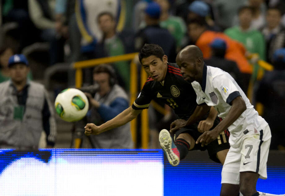 Mexico's forward Javier Aquino fights for the ball with U.S. defender DaMarcus Beasley. Photo: YURI CORTEZ, AFP/Getty Images / AFP