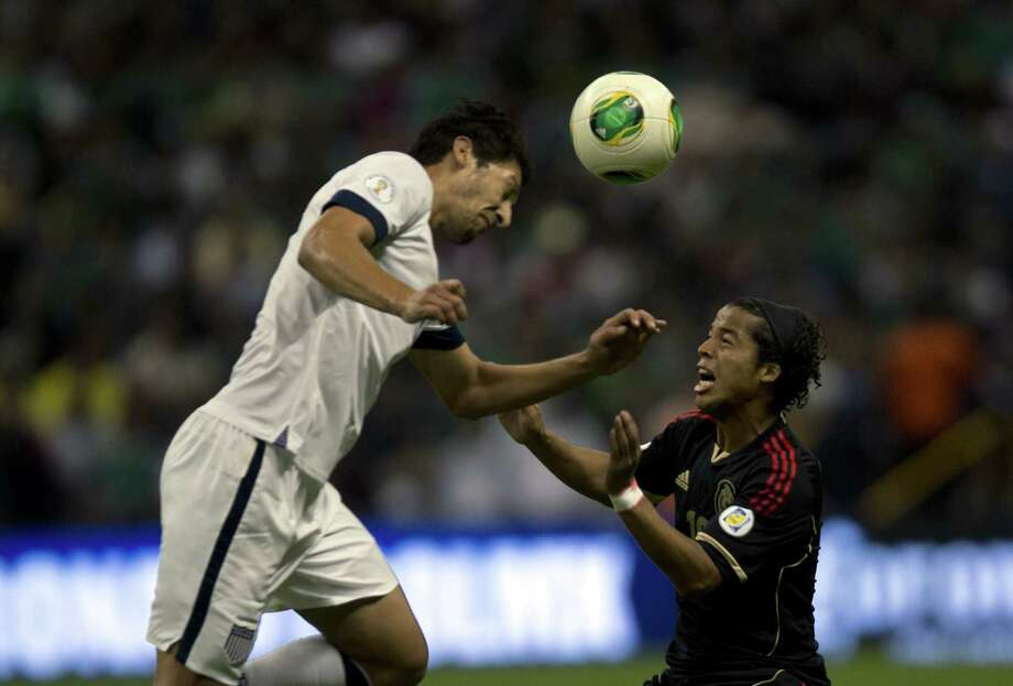 Mexico's forward Giovani Do Santos (R) disputes the ball with Omar Gonzalez (L) of the US during their 2014 World Cup qualifying football match at Azteca stadium in Mexico City, on March 26, 2013.  AFP PHOTO / Yuri CORTEZYURI CORTEZ/AFP/Getty Images Photo: YURI CORTEZ, AFP/Getty Images / YURI CORTEZ