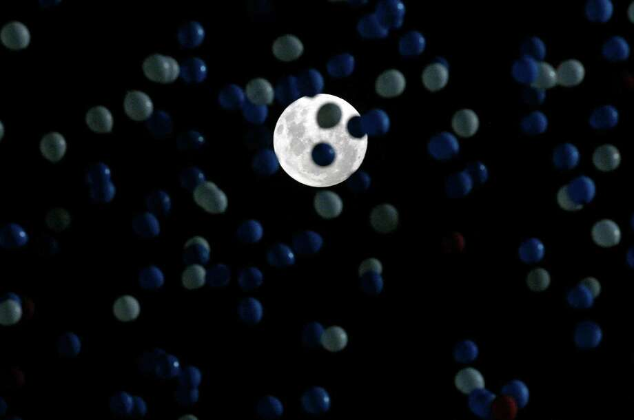 Backdropped by a full moon, thousands of balloons are released into the night sky honoring the Chilean soccer team at their 2014 World Cup qualifying soccer match against Uruguay in Santiago, Chile,  Tuesday, March 26, 2013. (AP Photo/Luis Hidalgo) Photo: Luis Hidalgo, Associated Press / AP