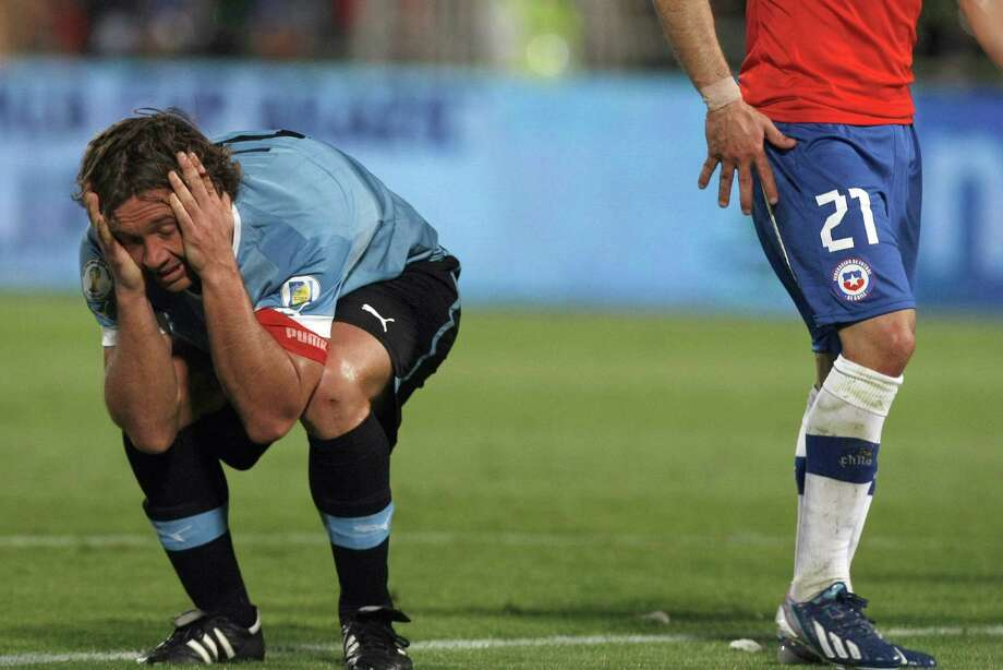Uruguay's Diego Lugano reacts after the referee didn't rule a foul during a 2014 World Cup qualifying soccer match against Chile in Santiago, Chile, Tuesday, March 26, 2013. (AP Photo/Luis Hidalgo) Photo: Luis Hidalgo, Associated Press / AP