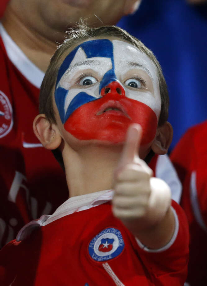 A young fan with his face painted with the colors of Chile's national flag gestures before the start of a 2014 World Cup qualifying soccer match against Uruguay in Santiago, Chile,  Tuesday, March 26, 2013. (AP Photo/Victor R. Caivano) Photo: Victor R. Caivano, Associated Press / AP