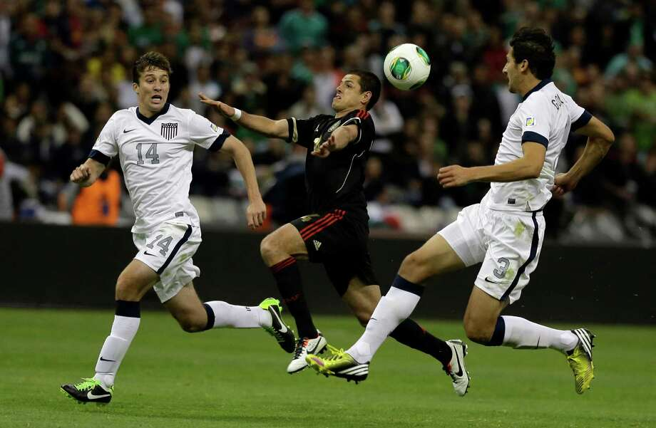 Mexico's Javier Hernandez, center, struggles to control the ball as he's pressured by United States' Matt Besler, left, and Omar Gonzalez during a 2014 World Cup qualifying match at the Aztec stadium in Mexico City, Tuesday, March 26, 2013. The game ended 0-0. (AP Photo/Eduardo Verdugo) Photo: Eduardo Verdugo, Associated Press / AP