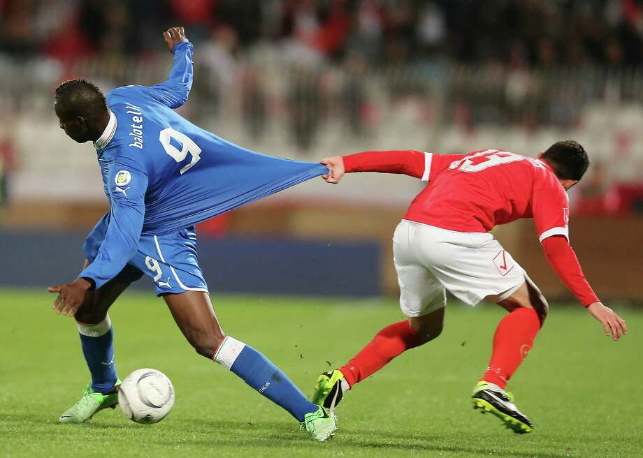 Malta midfielder Andre Schembri, right, pulls Italy forward Mario Balotelli's jersey during a World Cup Group B qualifying soccer match between Malta and Italy at the National Stadium Ta' Qali in Valletta, Malta, Tuesday, March 26, 2013. (AP Photo/Antonio Calanni) Photo: Antonio Calanni, Associated Press / AP