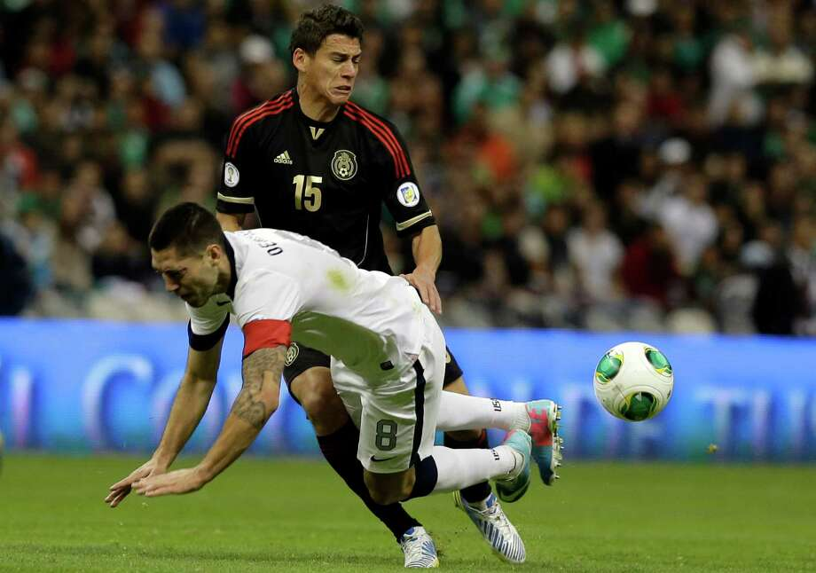 United States captain Clint Dempsey, left, is tackled by Mexico's Hector Moreno during a 2014 World Cup qualifying match at the Aztec stadium in Mexico City, Tuesday, March 26, 2013. (AP Photo/Eduardo Verdugo) Photo: Eduardo Verdugo, Associated Press / AP