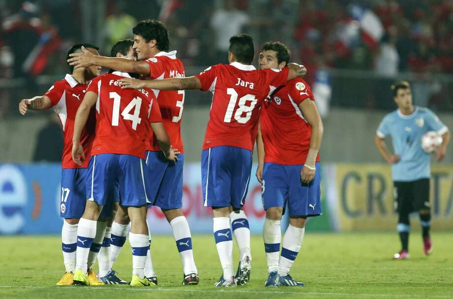 Chile's players celebrate at the end of a 2014 World Cup qualifying soccer match against Uruguay in Santiago, Chile,  Tuesday March 26, 2013. Chile won 2-0. (AP Photo/Victor R. Caivano) Photo: Victor R. Caivano, Associated Press / AP