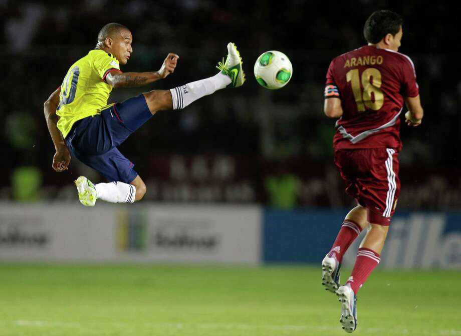 Colombia's Macnelly Torres, left, jumps to control the ball as Venezuela's Juan Arango reacts during a World Cup 2014 qualifying soccer match in Puerto Ordaz, Venezuela, Tuesday, March 26, 2013. (AP Photo/Fernando Llano) Photo: Fernando Llano, Associated Press / AP