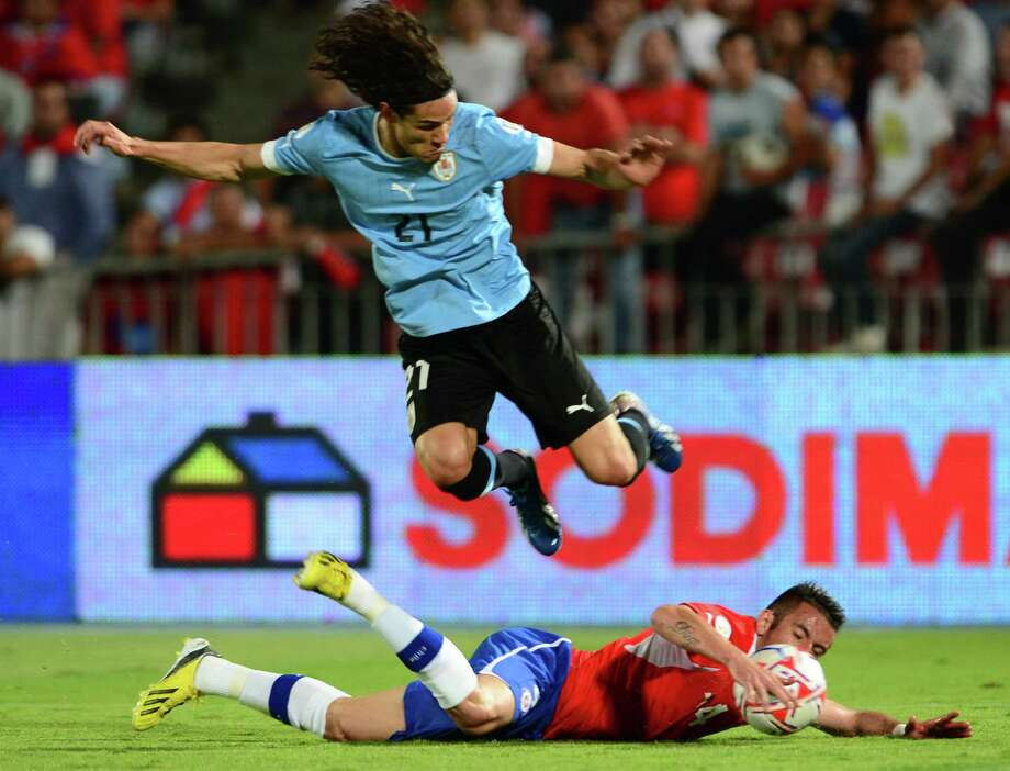 Chilean defender Mauricio Isla (bottom) vies for the ball with Uruguayan forward Edinson Cavani during their FIFA World Cup Brazil 2014 South American qualifying football match in Santiago, Chile on March 26, 2013. AFP PHOTO / MARTIN BERNETTIMARTIN BERNETTI/AFP/Getty Images Photo: MARTIN BERNETTI, AFP/Getty Images / AFP
