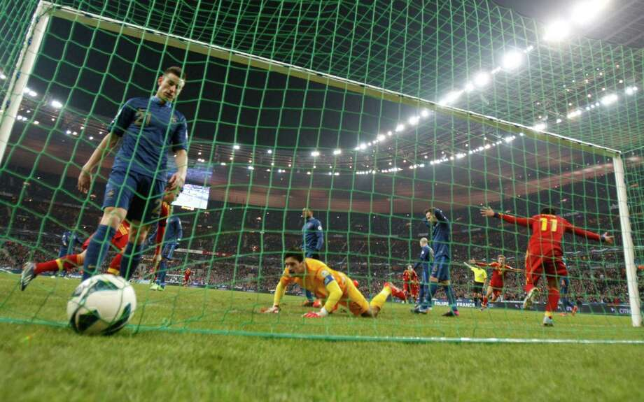 France's goalkeeper Hugo Lloris, center, lies one pitch after Spain's Pedro Rodriguez Ledesma, right, scores during their World Cup 2014 qualifying soccer match at the Stade de France in Saint Denis, north of Paris, Tuesday, March 26, 2013. (AP Photo/Christophe Ena) Photo: Christophe Ena, Associated Press / AP
