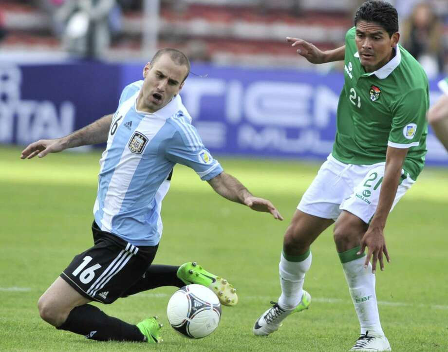 Argentina's Rodrigo Palacio (L) vies for the ball with Bolivia's Edward Zenteno during their Brazil 2014 FIFA World Cup South American qualifier football match, at the Hernando Siles stadium in La Paz, on March 26, 2013. The match ended 1-1. AFP PHOTO / AIZAR RALDESAIZAR RALDES/AFP/Getty Images Photo: AIZAR RALDES, AFP/Getty Images / AFP