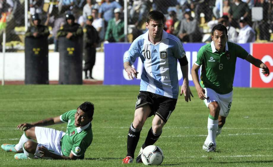 Argentina's Lionel Messi (C) controls the ball next to Bolivia's Bolivia's Walter Veizaga (R) during their Brazil 2014 FIFA World Cup South American qualifier football match, at the Hernando Siles stadium in La Paz, on March 26, 2013. The match ended 1-1. AFP PHOTO / AIZAR RALDESAIZAR RALDES/AFP/Getty Images Photo: AIZAR RALDES, AFP/Getty Images / AFP