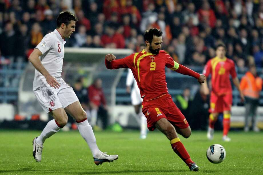 Montenegro's Mirko Vucinic, center, goes with the ball past England's Michael Carrick. left, during their World Cup Group H qualifying match in Podgorica, Montenegro, Tuesday, March 26, 2013. (AP Photo/ Marko Drobnjakovic) Photo: Marko Drobnjakovic, Associated Press / AP