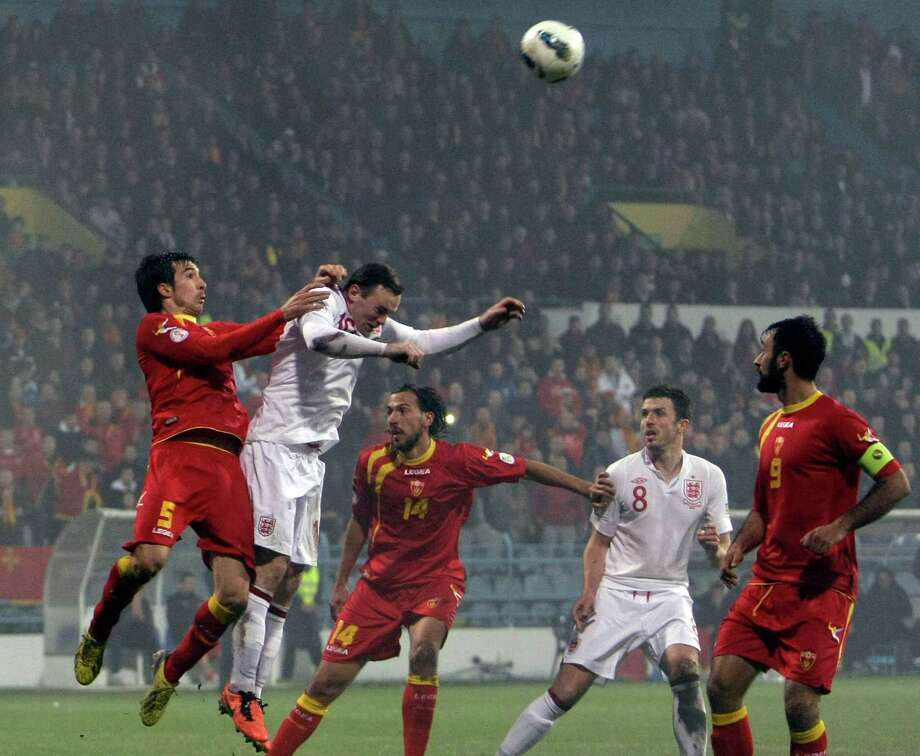 England's Wayne Rooney, center left, and Montenegro's Vladimir Volkov, 3rd right, jump for a ball during their World Cup Group H qualifying match in Podgorica, Montenegro, Tuesday, March 26, 2013. (AP Photo/ Marko Drobnjakovic) Photo: Marko Drobnjakovic, Associated Press / AP