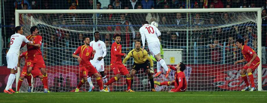 England's forward Wayne Rooney (3rdR) jumps to score a goal during the World Cup 2014 qualifying football match Montenegro vs England at Podgorica stadium in Podgorica on March 26, 2013.    AFP PHOTO / DIMITAR DILKOFFDIMITAR DILKOFF/AFP/Getty Images Photo: DIMITAR DILKOFF, AFP/Getty Images / AFP
