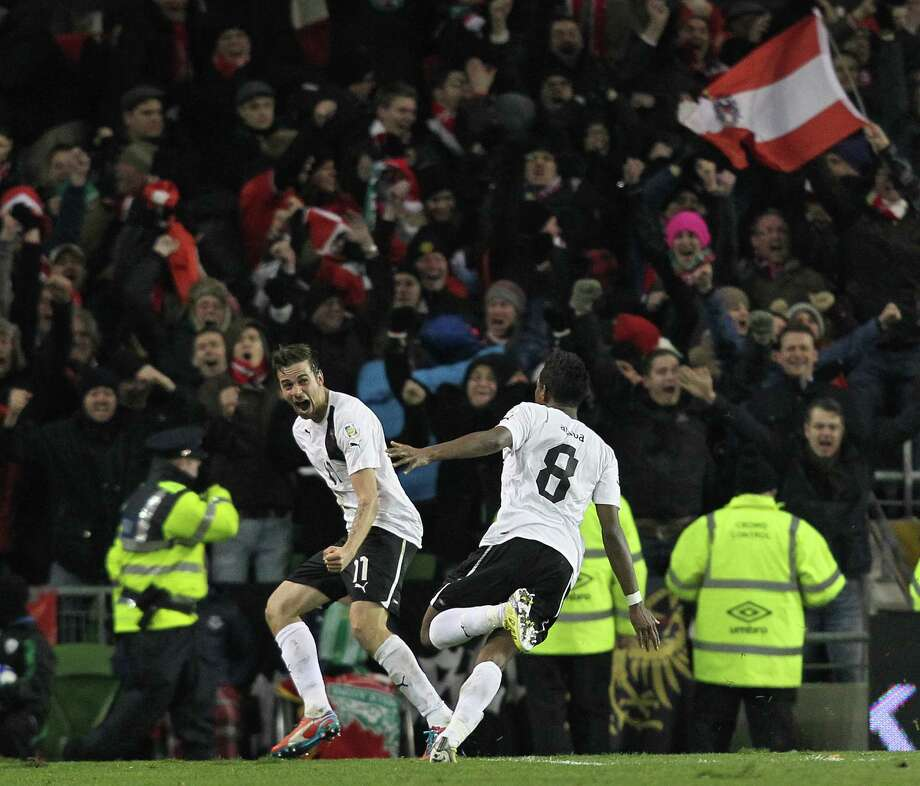 David Alaba (R) and Martin Harnik (L) of Austria celebrate in front of Austrian supporters after Alaba's late equalizer in the FIFA 2014 World Cup qualifying football match between Republic of Ireland and Austria at Aviva Stadium in Dublin, Ireland, on March 26, 2013. The game finished 2-2. AFP PHOTO/PETER MUHLYPETER MUHLY/AFP/Getty Images Photo: PETER MUHLY, AFP/Getty Images / AFP