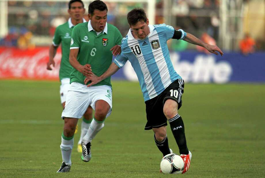 Argentina's Lionel Messi, right, fights for the ball with Bolivia's Walter Veizaga during a World Cup 2014 qualifying soccer match in La Paz, Bolivia, March 26, 2013. (AP Photo/Juan Karita) Photo: Juan Karita, Associated Press / AP