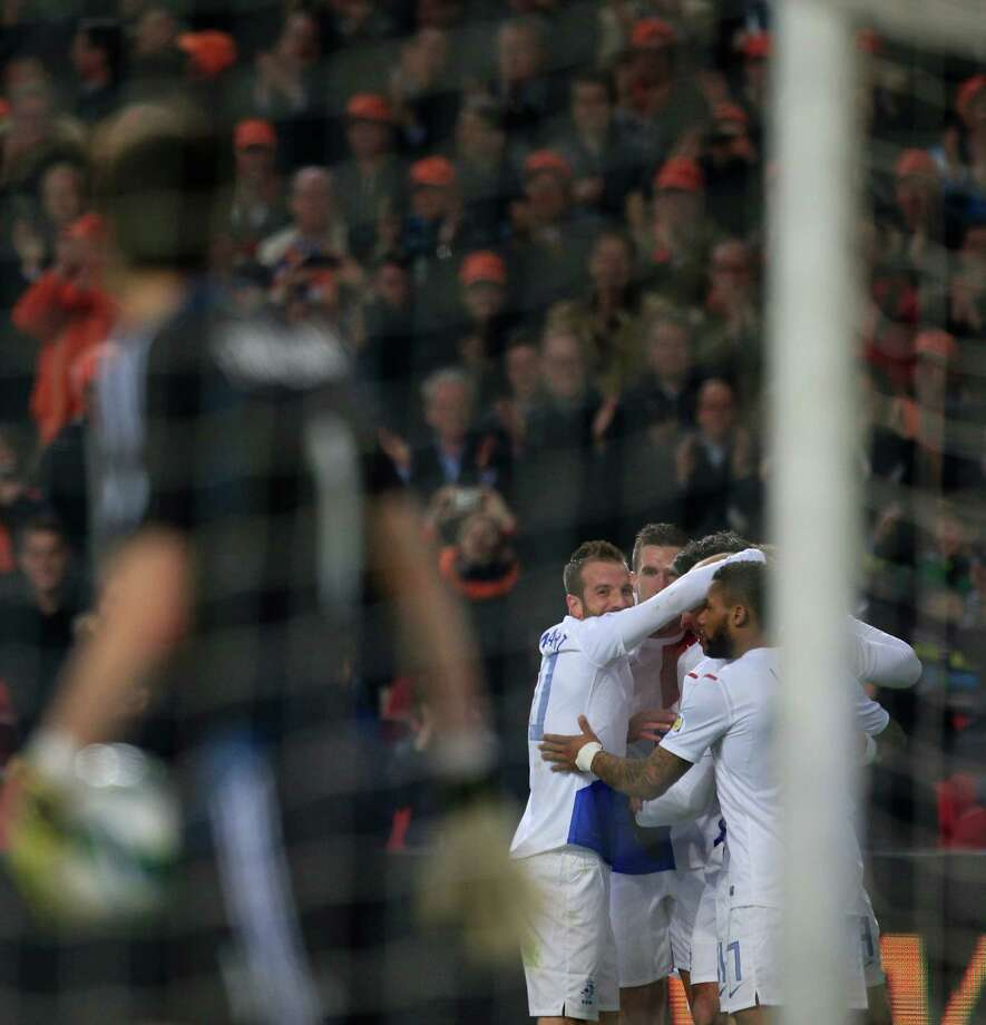 Goalkeeper Costel Fane Pantilimon of Romania, left, looks at Dutch players Rafael van der Vaart, rear left, Robin van Persie, rear center, and Jeremain Lens, rear right,  celebrating as he walks away with the ball after The Netherlands scored during the Group D World Cup qualifying soccer match Netherlands against Romania at ArenA stadium in Amsterdam, Netherlands, Tuesday March 26, 2013. The Dutch won the match with a 4-0 score. (AP Photo/Peter Dejong) Photo: Peter Dejong, Associated Press / AP