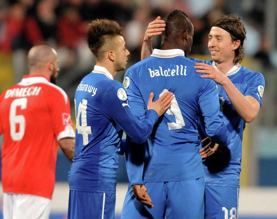 Italy's Mario Balotelli (C) is congratulated by team mates Riccardo Montolivo (R) and Stephen El Shaarawy (left) during the FIFA 2014 World Cup qualifying football match Malta vs.Italy at the National Stadium in Malta on March 26, 2013.  AFP PHOTO / MATTHEW MIRABELLIMatthew Mirabelli/AFP/Getty Images Photo: MATTHEW MIRABELLI, AFP/Getty Images / AFP