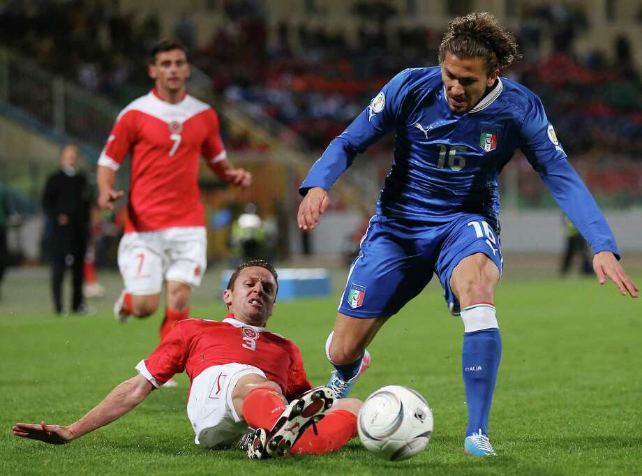 Italy midfielder Alessio Cerci, right, is tackled by Malta defender Alexander Muscat during the World Cup Group B qualifying soccer match between Malta and Italy at the National Stadium Ta' Qali in Valletta, Malta, Tuesday, March 26, 2013. (AP Photo/Antonio Calanni) Photo: Antonio Calanni, Associated Press / AP