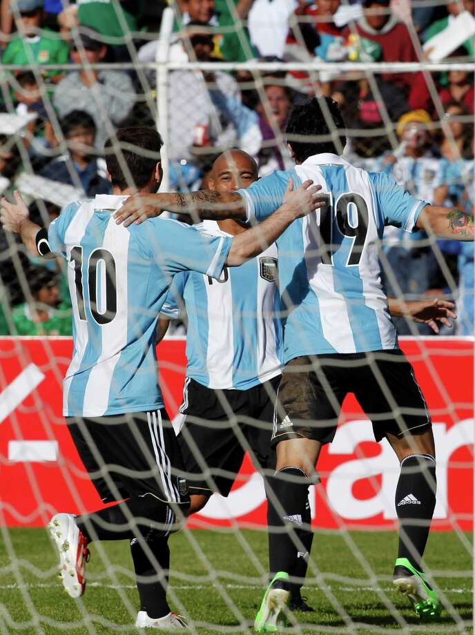 Argentina's Ever Banega, right, celebrates with his teammates Clemente Rodriguez, center, and Lionel Messi, after Ever scored a goal against Bolivia during a 2014 World Cup qualifying soccer game in La Paz, Bolivia, Tuesday, March 26, 2013. (AP Photo/Martin Mejia) Photo: Martin Mejia, Associated Press / AP