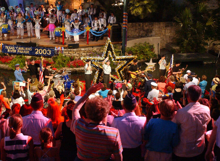 Fiesta River Parade 2003: The crowd comes to its feet as the float from Fort Sam Houston passes by. Photo: San Antonio Express-News File Photo / SAN ANTONIO EXPRESS-NEWS