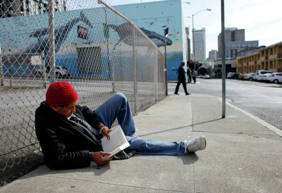 Jeffry Moore, 63, is homeless and spends a recent morning reading John Lescroart's The Second Chair as he sits along Olive Street. I found this book and it gives me something to do with my time, said Moore. Photo: Lacy Atkins, The Chronicle / ONLINE_YES