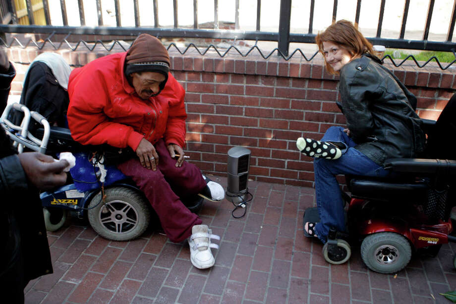Doc Goss, left, and his friend Bobby Lunceford, 53, sit in their electric chairs on Eddy Street in San Francisco talking over the difficulties of being homeless. Photo: Jessica Olthof, The Chronicle / ONLINE_YES