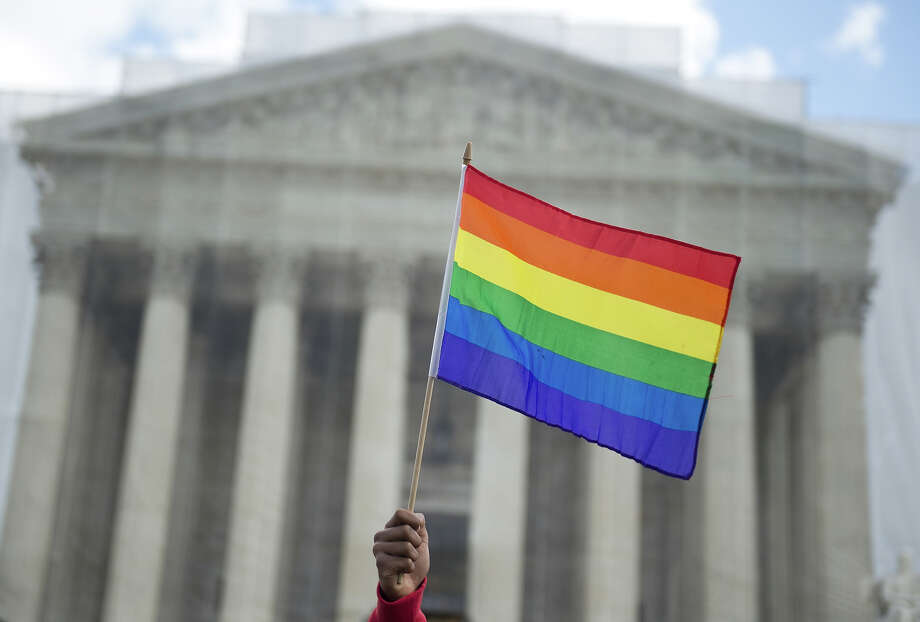 A same-sex marriage supporter waves a rainbow flag in front of the US Supreme Court on March 26, 2013 in Washington, DC, as the Court takes up the issue of gay marriage. The US Supreme Court on Tuesday heard arguments on the emotionally charged issue of gay marriage as it considers arguments that it should make history and extend equal rights to same-sex couples. Waving US and rainbow flags, hundreds of gay marriage supporters braved the cold to rally outside the court along with a smaller group of opponents, some pushing strollers. Some slept outside in hopes of witnessing the historic hearing. Photo: SAUL LOEB, AFP/Getty Images / 2013 AFP