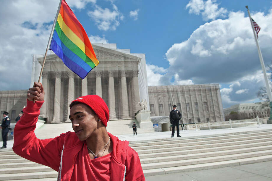 A young man holds a rainbow flag in front of the US Supreme Court in Washington on March 26, 2013 as the court hears arguments on California's Proposition 8 ban on same-sex marriage. Photo: NICHOLAS KAMM, AFP/Getty Images / 2013 AFP