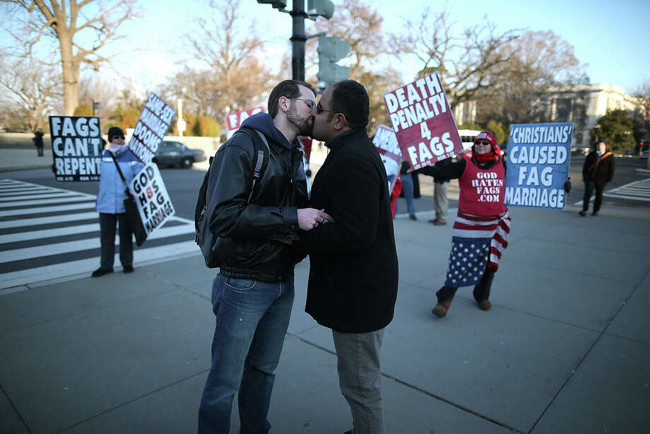 Married couple Nathan Lents (L) and Oscar Cifuentes kiss in front of Westboro Baptist Church protesters, in front of the U.S. Supreme Court, on March 27, 2013 in Washington, DC. Today the high court is scheduled to hear arguments on whether Congress can withhold federal benefits from legally wed gay couples by defining marriage as only between a man and a woman. Photo: Mark Wilson, Getty Images / 2013 Getty Images