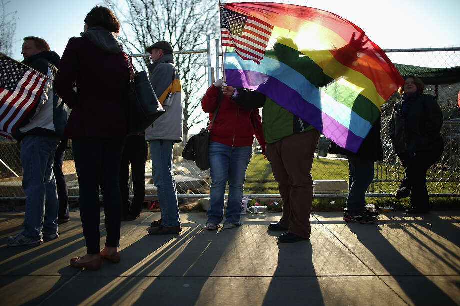 Heather Davidson and Julie Berger (C), both of Shelbyville, Indiana, hold up a pride flag while standing in line with hundreds of others outside the Supreme Court for a chance to hear oral arguments March 27, 2013 in Washington, DC. The Supreme Court will hear arguments in the second case this week about same-sex marriage. Photo: Chip Somodevilla, Getty Images / 2013 Getty Images