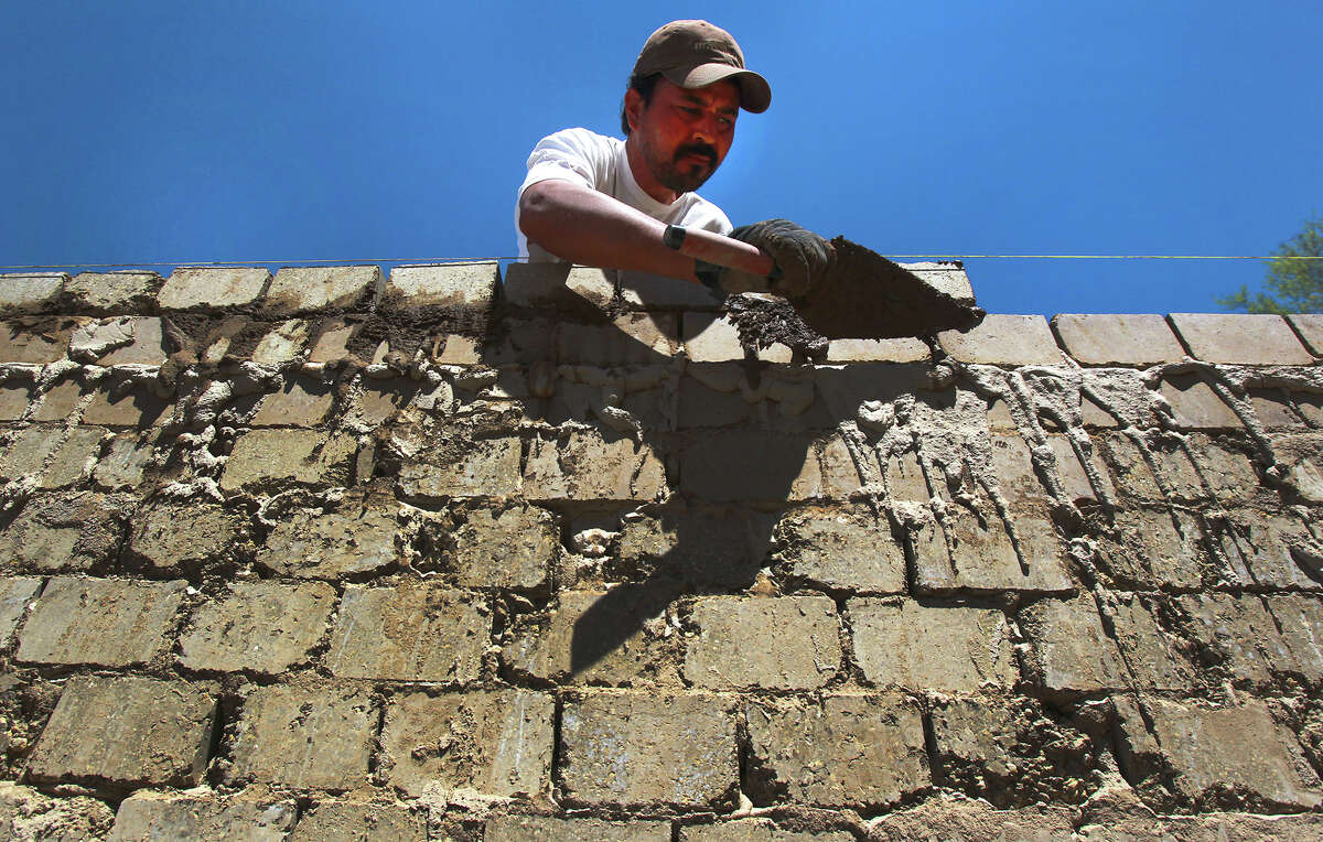 Isidro Hernandez lays compressed earth blocks on a wall of an apartment building on Eisenhauer Road. Urban Earth is building apartments designed by Lake|Flato with compressed earth block.