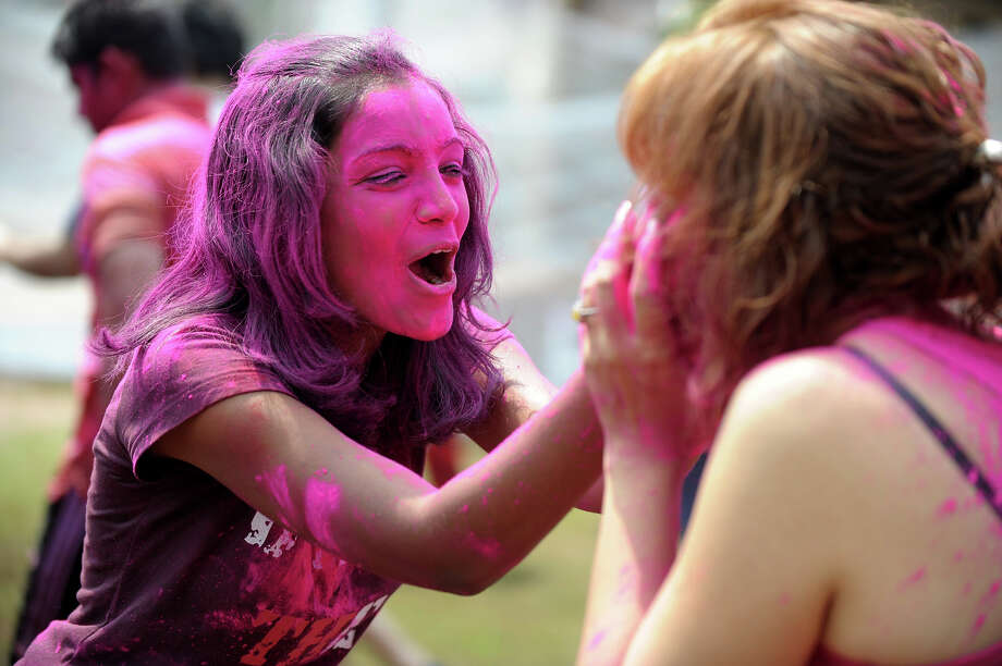 Indian revelers play with colored powder during Holi celebrations in Hyderabad on March 27, 2013.  Holi, also called the Festival of Colors, is a popular Hindu spring festival observed in India at the end of the winter season on the last full moon day of the lunar month. Photo: NOAH SEELAM, AFP/Getty Images / 2013 AFP