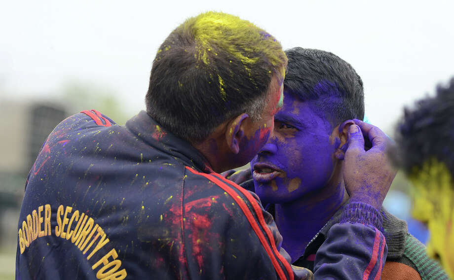 Indian Border Security Force Soldier (BSF) soldier cover each other with colored powder as they celebrate during the Holi festival inside a camp in Srinagar on March 27, 2013.  Holi, also called the Festival of Colors, is a popular Hindu spring festival observed in India at the end of the winter season on the last full moon day of the lunar month. Photo: TAUSEEF MUSTAFA, AFP/Getty Images / 2013 AFP