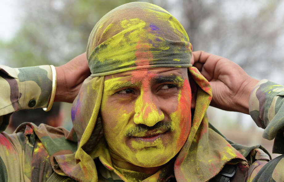 An Indian Border Security Force Soldier (BSF)with colored powder celebrates during the Holi festival inside a camp in Srinagar on March 27, 2013.  Holi, also called the Festival of Colors, is a popular Hindu spring festival observed in India at the end of the winter season on the last full moon day of the lunar month. Photo: TAUSEEF MUSTAFA, AFP/Getty Images / 2013 AFP
