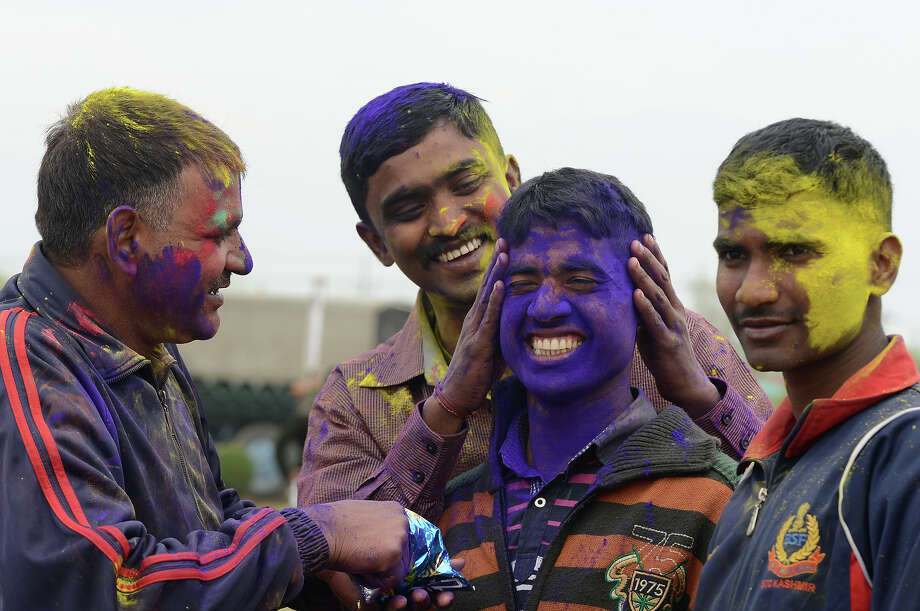 Indian Border Security Force Soldiers (BSF) cover each other with colored powder as they celebrate during the Holi festival inside a camp in Srinagar on March 27, 2013.  Holi, also called the Festival of Colors, is a popular Hindu spring festival observed in India at the end of the winter season on the last full moon day of the lunar month. Photo: TAUSEEF MUSTAFA, AFP/Getty Images / 2013 AFP