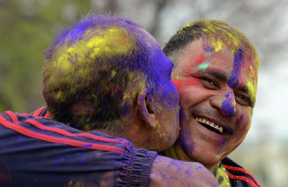 Indian Border Security Force Soldiers (BSF) their faces covered with colored powder embrace as they celebrate during the Holi festival inside a camp in Srinagar on March 27, 2013.  Holi, also called the Festival of Colors, is a popular Hindu spring festival observed in India at the end of the winter season on the last full moon day of the lunar month. Photo: TAUSEEF MUSTAFA, AFP/Getty Images / 2013 AFP