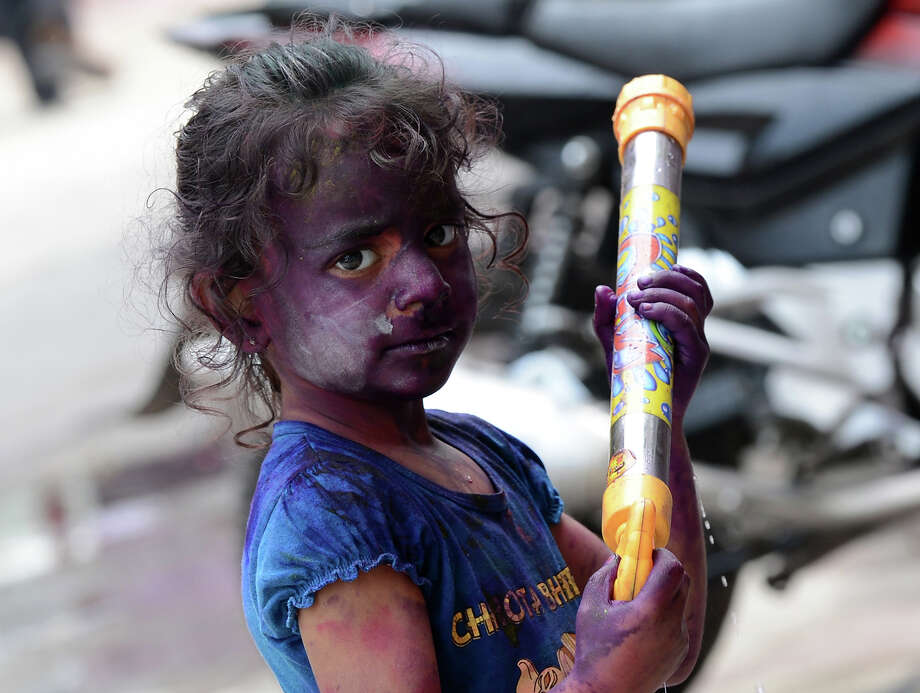 A young Indian reveler plays with colored powder during Holi celebrations in New Delhi on March 27, 2013. Holi, also called the Festival of Colors, is a popular Hindu spring festival observed in India at the end of the winter season on the last full moon day of the lunar month. Photo: SAJJAD HUSSAIN, AFP/Getty Images / 2013 AFP