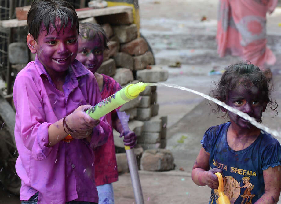 Indian children play with colored water during Holi celebrations in New Delhi on March 27, 2013. Holi, also called the Festival of Colors, is a popular Hindu spring festival observed in India at the end of the winter season on the last full moon day of the lunar month. Photo: SAJJAD HUSSAIN, AFP/Getty Images / 2013 AFP