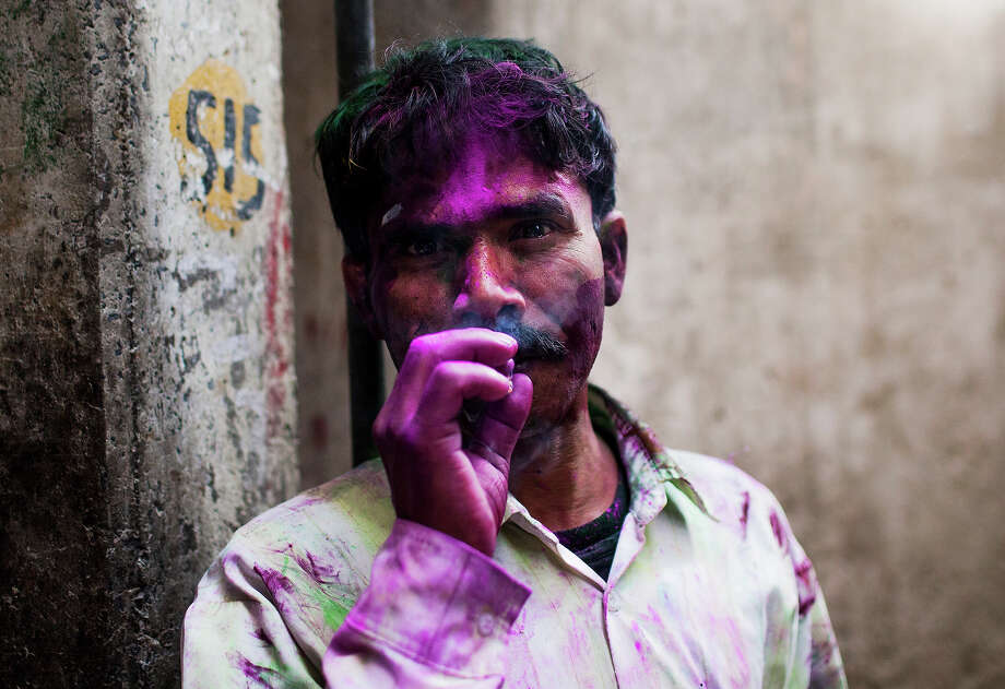 An Indian youth covered with colored powder smokes in an alleyway during Holi celebrations in New Delhi on March 27, 2013. 'Holi', the Festival of Colors, is a popular Hindu spring festival observed in India and Nepal at the end of winter season on the last full moon day of the lunar month. Photo: AFP, AFP/Getty Images / 2013 AFP