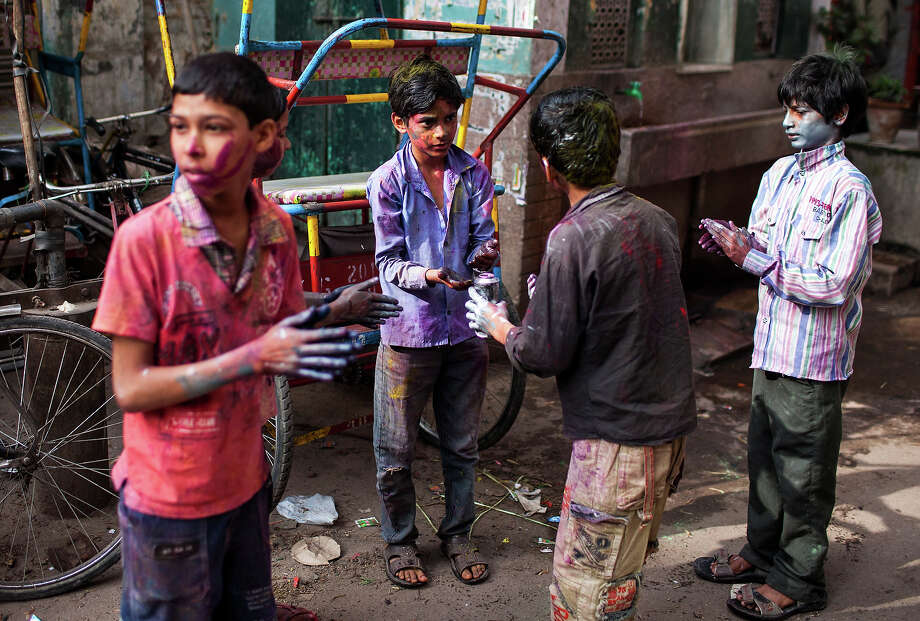 Young Indian youth cover themselves with colored powder during Holi celebrations in New Delhi on March 27, 2013. 'Holi', the Festival of Colors, is a popular Hindu spring festival observed in India and Nepal at the end of winter season on the last full moon day of the lunar month. Photo: AFP, AFP/Getty Images / 2013 AFP