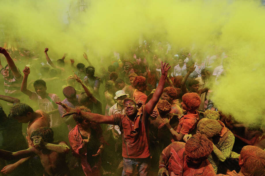 Indian revelers cover each other with colored powder during Holi festival celebrations in Guwahati on March 27, 2013. 'Holi', the Festival of Colors, is a popular Hindu spring festival observed in India and Nepal at the end of winter season on the last full moon day of the lunar month. Photo: AFP, AFP/Getty Images / 2013 AFP